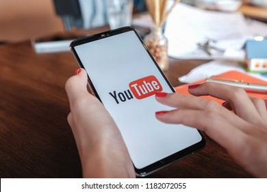 CHIANGMAI,THAILAND - Sep 09, 2018: A woman showing screen shot of Youtube on Oneplus6 digital mobile YouTube app on the screen lying on old wood desk. YouTube is the popular online video sharing