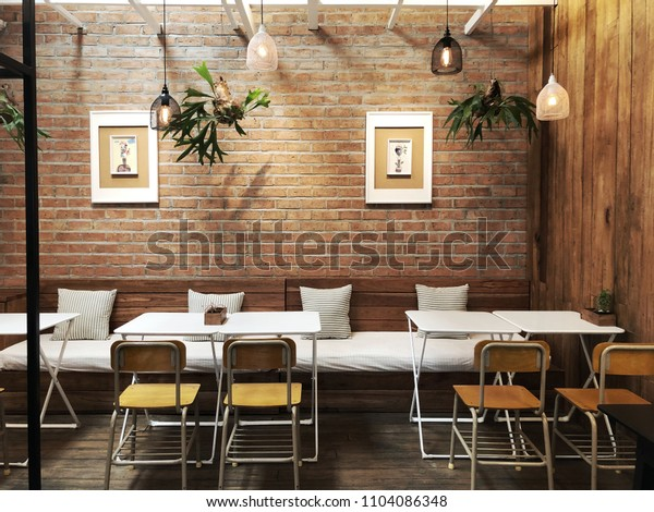 Chiangrai, Thailand; 23 May 2018: Modern cafe interior with a brick wall, a white tables, white sofas. The interior design of a Coffee shop, cafe.