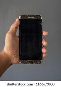Chiangrai, Thailand: December 4, 2018 - Human hand holding broken smartphone Samsung Galaxy S7 edge