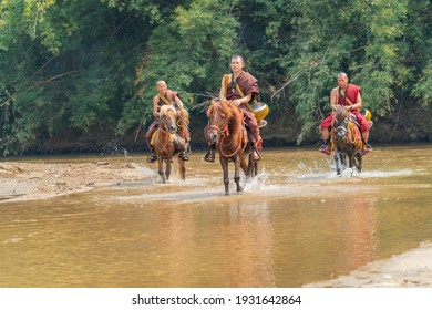 Chiangrai, Thailand - February 16, 2019: Buddhist monks from Wat Thumpa Achathong riding horses to receive food offering in Chiangrai, Thailand