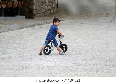 Chiang-rai, Thailand - Oct 13, 2017: Asian boy in blue shirt on the strider balance bike without helmet in chiang-rai, Thailand on October 13, 2017