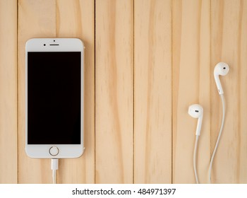 CHIANGRAI, THAILAND -SEPTEMBER 15, 2016: Front view image of new Apple iPhone7 mockup and new Apple EarPods mockup on wooden background with copy space.