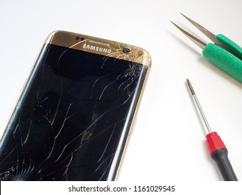 Chiangrai, Thailand: September 20, 2017 - Smart phone Samsung Galaxy S7 edge broken and cracked screen with screwdriver and tweezers prepairing to repair on white background