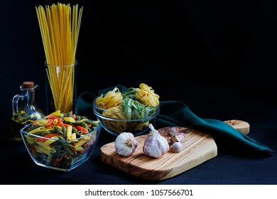 Chiaroscuro Dark Food Pasta ingredients with spaghetti,  tagliatelle and penne tricolore and garlic with olive oil with copy space