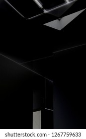 Chiaroscuro photo of a dark room with ceiling window. Abstract black and white modern architecture background in grunge style. Mysterious / enigmatic interior.