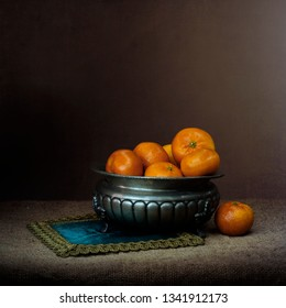 Chiaroscuro style still life with oranges in pewter bowl. Retro.