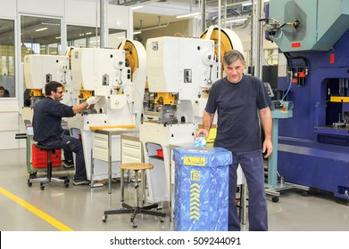 Chiasso, Switzerland - 13 January 2014: man who is recycling a bottle of pet into the appropriate container in the industry hall