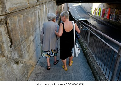 CHIAVARI, ITALY-JULY 23, 2018: polish female caregiver walking and supporting an italian old lady , in Chiavari.