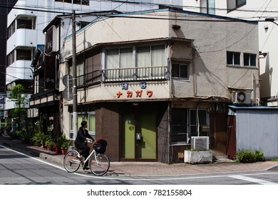 CHIBA, JAPAN - April 18, 2017: A cyclist rides past a now-closed barber shop in a Showa-era building. A traditional restaurant can be seen in the sandwiched between it and a large modern one.