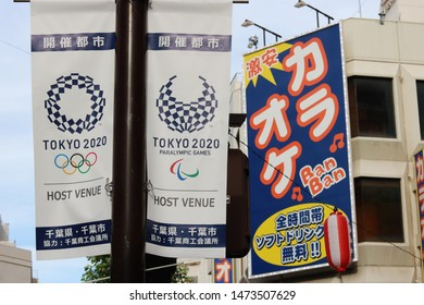 CHIBA, JAPAN - August 8, 2019: Banners promoting Tokyo Olympics & Paralympics on a streetlight. Chiba City will host some events incl. fencing. A billboard on a karaoke center is in the background.