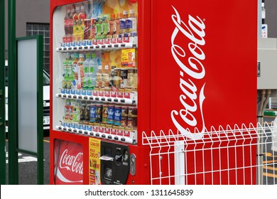 CHIBA, JAPAN - December 25, 2018: A drinks vending machine with Coca Cola design in front of a parking lot in Chiba City. It's winter so hot and cold drinks are offered.