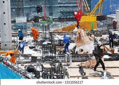 CHIBA, JAPAN - February 11, 2019: Workers on a construction site for a large multi-purpose building (shopping centre, apartments etc.) in Chiba City during heavy snowfall. Some motion blur.