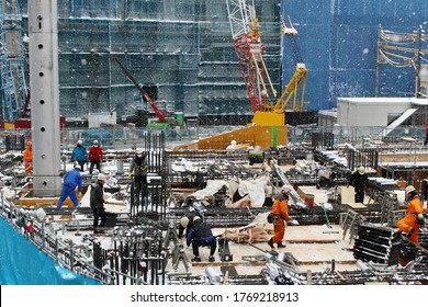 CHIBA, JAPAN - February 11, 2019: Workers on a construction site for a large multi-purpose building (Shin Nihon EX Biru) in Chiba City during heavy snowfall. Some motion blur.