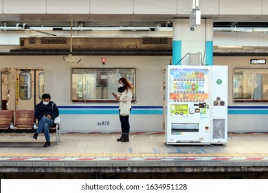 CHIBA, JAPAN - February 4, 2020: People waiting on station platform wearing face masks use smartphones. The station in Chiba Prefecture is a terminal station on Tokyo Metro's Tozai Line.