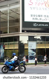 CHIBA, JAPAN - July 12, 2018: Waiting pedestrians look at smartphones at a crossing by a Lexus showroom with giant screen reminding people not to use smartphones while walking. Some motion blur.
