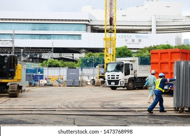 CHIBA, JAPAN - July 23, 2019: A worker opens a gate to allow a truck to leave a large-scale building site in Chiba City. Chiba Station and monorail tracks leading to it are in the background.