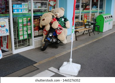 CHIBA, JAPAN - July 26, 2019: A pair of giant soft toys, a dog and a bear, wearing summer shirts on a miniature motorcycle in front of a FamilyMart convenience store in Chiba City.