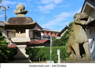 CHIBA, JAPAN - July 26, 2019: A komainu statue (lion dog) and stone lantern at a Shinto Shrine in suburban Chiba City.