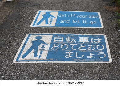 CHIBA, JAPAN - July 30, 2020:  Notices on a street in Chiba City at the top of a slope asking cyclists to dismount before descending. The English version appears to be a mistranslation.