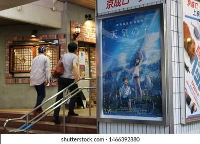 CHIBA, JAPAN - July 31, 2019: The entrance to Keisei Chiba train station with pedestrians and a movie poster advertising the movie 'Weathering with You'. Some motion blur.