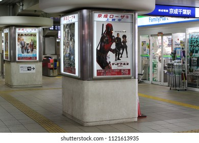 CHIBA, JAPAN - June 26, 2018: View of the interior of Chiba Keisei line train station with a Familymart convenience store & pillars carrying adverts for movies on locally including Deadpool 2.