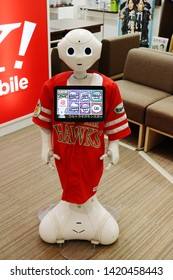 CHIBA, JAPAN - June 7, 2019: A Softbank Pepper robot on customer service at the front of a Softbank store in Makuhari. It's wearing a Softbank Hawks uniform, a baseball team sponsored by the company.