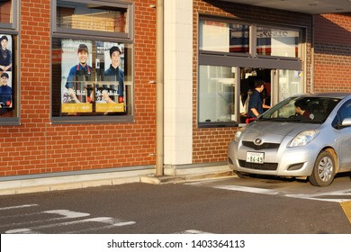 CHIBA, JAPAN - May 11, 2019: A car at the Part of a McDonalds restaurant with drive-thru section.It is located in Naruto in Sanmu City.  There are staff wanted posters in the store's windows.