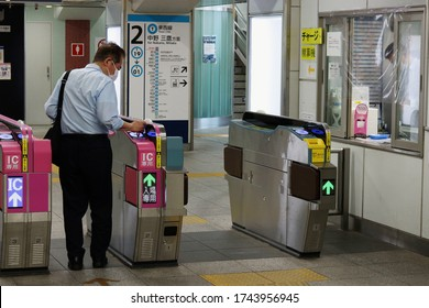 CHIBA, JAPAN - May 29, 2020: A passenger uses IC card ticket gate at a Tozai Line station. People wear face masks & there is a plastic shield over the ticket gate window during coronavirus outbreak.