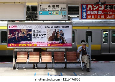 CHIBA, JAPAN - October 27, 2018: A Nishi Funabashi station platform. The station serves both the Tokyo Metro subway system as well as various overground lines. A moving JR train is in the background.