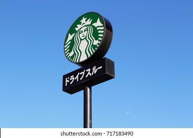 CHIBA, JAPAN - September 18, 2017: A tall sign outside a Drive-thru Starbucks coffee shop beside a main road in Chiba City. The sign in katakana below the Starbucks logo reads 'doraibusuru-'.