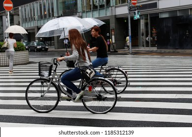 CHIBA, JAPAN - September 6, 2017 - A pair of cyclists sheltering from the rain under umbrellas while riding through downtown Chiba City. Some motion blur.