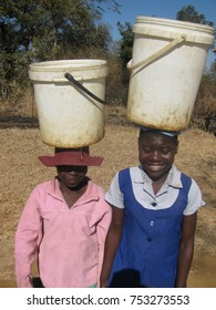 Chibero,Zimbabwe,9September 2016.Two  young African  girls  carrying  buckets  of  water  on  their heads.Many women walk long  distances to  get water Africa.