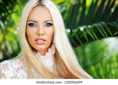 Chic blonde woman on nature background. Close up portrait