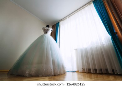 chic bride dress on the mannequin in the bright room with a large window.