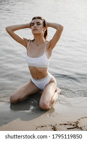 Chic brunette in white bikini sits on sandy river bank and holds her hands to her head