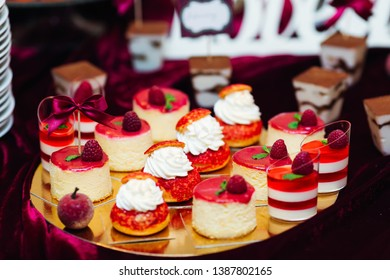chic desserts on the tray are decorated with raspberries. wedding