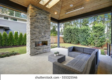 Chic, elegant deck patio design features vaulted paneled ceiling with skylights over a floor to ceiling gray stone fireplace and large taupe wicker sofa with ottoman as coffee table. Northwest, USA