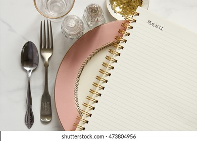 """Chic and elegant pink table top setting with silverware, salt and pepper, bowl of glitter, glass over marble with blank notebook with the word """"MENU"""" printed on top"""