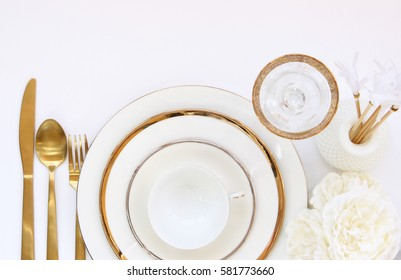 Chic and elegant white and gold table setting frames empty white space for copy.