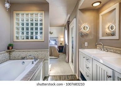 Chic ensuite bathroom with his and hers sinks, white drop-in tub with natural stone tile surround and taupe walls. Northwest, USA