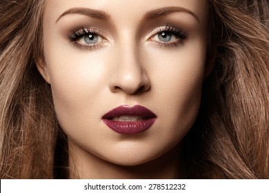 Chic evening style. Alluring woman model with luxury fashion make-up, dark red lips makeup and long hair. Trends colors, marsala wine color lipstick, strong eyebrows, sexy hair