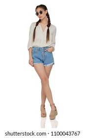 A chic girl with long braided hair, wearing sunglasses, a white shirt, raw hem denim shorts, wedge sandals. The young woman standing over the white background, one hand in the pocker, legs crossed.