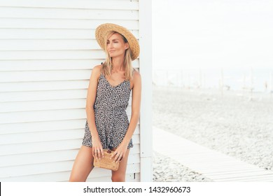 Chic gorgeous tanned blonde girl in a leopard print overalls is standing on a white background by the sea, summer hot day, vacation concept. Copy space for text. Fashion vogue and trend this season.