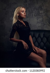 Chic graceful blod model sitting in fashion armchair in black dress and posing on dark dramatic background