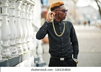Chic handsome african american man in black shirt with gold chain and sunglasses.