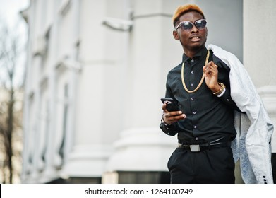 Chic handsome african american man in white suit and black shirt with mobile phone.