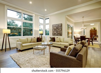 Chic light living room design with dark floors. Furnished with glass top accent tables and beige sofas topped with brown pillows . Northwest, USA
