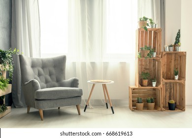 Chic living room with elegant armchair and wooden DIY shelf