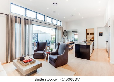 Chic décor for living room, two high sofa chairs with a table, attached to the kitchen.