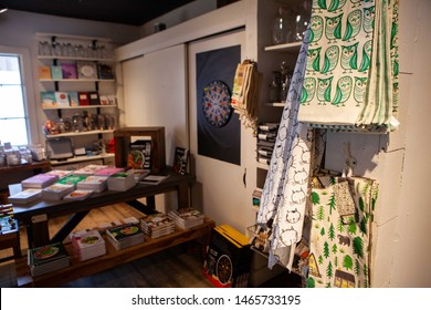 Chic patterned textile in homeware shop. A close up view of kitchen dish drying towels with unique nature patterns are seen hanging inside an ecofriendly store, books on shelves are seen in background